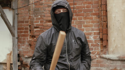 Aggressive hooligan in mask threatening to camera with baseball bat Live Action
