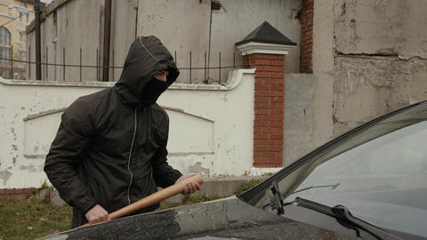 Aggressive vandal in mask and hood going to crash car with baseball bat on Live Action
