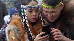 Woman in national clothing indigenous inhabitants reads messages in smartphone Live Action