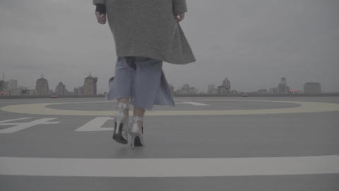 Woman in silver shoes goes against the background of urban buildings. S-log Footage