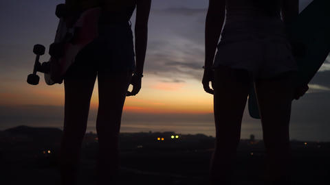 Girlfriends look at the beautiful view of the sunset sky after skateboarding on Footage