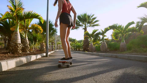 woman ride at sunset smiling with boards for skate Board along the path in the Live Action