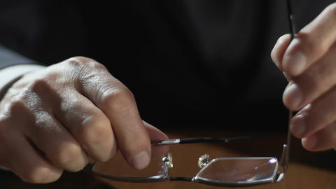 Hands of adult businessman holding eyeglasses and putting it on table, lawyer Live Action
