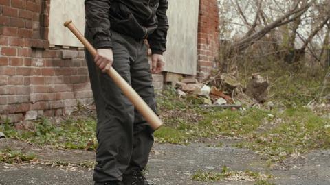 Masked bandit with baseball bat at abandoned place GIF