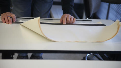 Man marks sheets of paper before cutting Footage