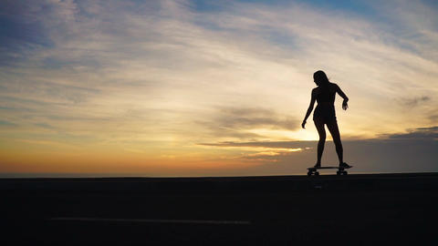 Close-up silhouette of skateboards against the sunset sky in slow motion. Feet Live Action