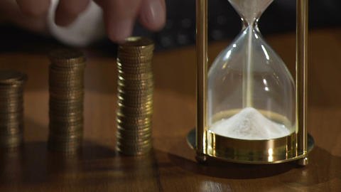 Rich man putting coins on piles, view on sandglass measuring time, finance Footage