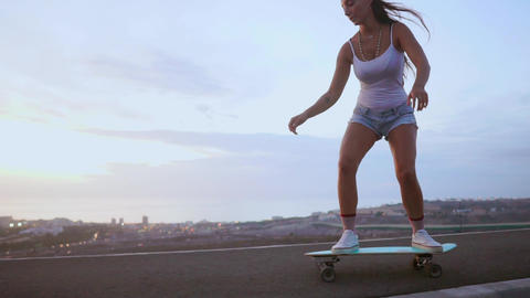 The girl is engaged in sports skateboarding with mountain Live Action