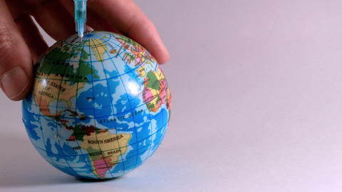 Plastic syringe injects poison into a globe, ideal footage to explain ecology GIF