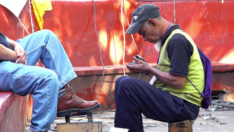 An old man works as shoe shine Footage
