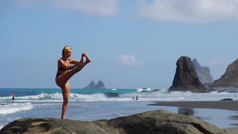 Young girl in bikini balancing standing on one leg doing yoga standing on a rock Live Action