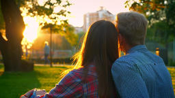 Two lovely people in love are sitting closely in amazing summer park, sun shines Footage