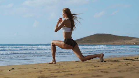 Sport girl on a beach doing lunges exercises. Concept of of a healthy lifestyle Live Action