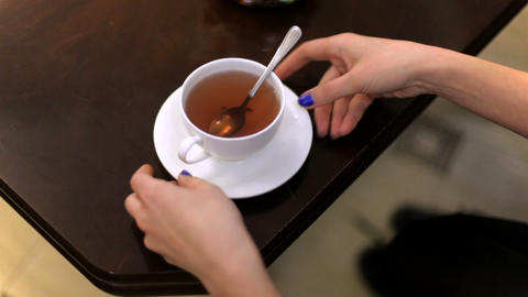 A girl is drinking tea from a white cup GIF