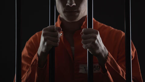 Thief in jail feeling sincere regret of crime, holding prison bars in desperate Live Action