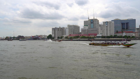 Cityscape of Bangkok at sunrise across the river with tourist long tail boats Live Action