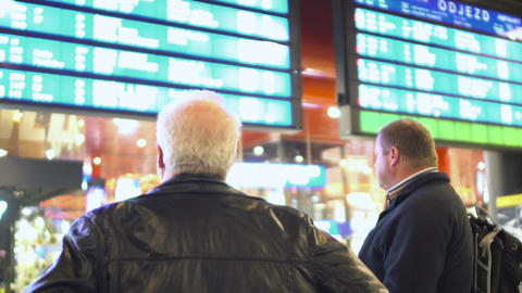 Men looking at schedule screen, waiting for their train to arrive, station Live Action