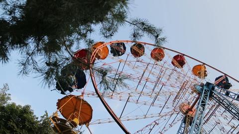 Ferris wheel slowly rotating in city park, passengers sitting cabin, bottom view Archivo