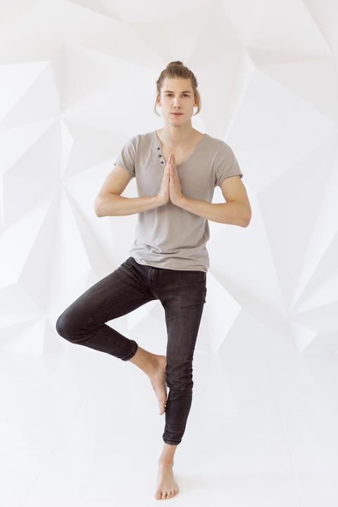 Man doing exercise on one leg on a white polygon background Photo