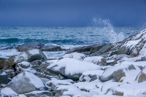 Snow-Covered Stones on the Ocean Coastline Photo