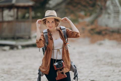 Cool funny girl model with elegant hat, brown jacket, curly hair outdoors Fotografía