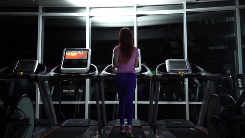 girl runs on the treadmill in night-time Footage