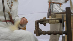 Spinning wheel. Woman is spinning wool and shows a woolen rug Live Action