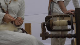 Woman is spinning wool on a spinning wheel. Slow motion Live Action