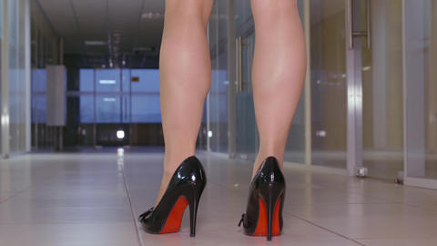 Female legs in high heeled shoes walking in hall at business office back view GIF