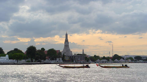 Wat Arun buddhist temple on Chao Phraya river at sunset, most popular sight in Live Action