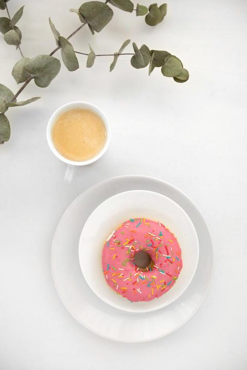 Plant twig near coffee and donut Photo