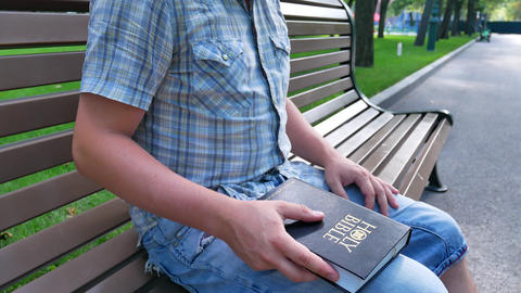 Man is holding Holy Bible in his hand sitting on a bench in a park in the summer Footage