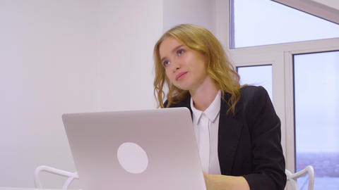 Happy business woman using laptop computer for work in business office Live Action