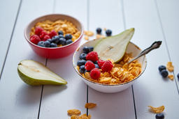 Golden cornflakes with fresh fruits of raspberries, blueberries and pear in Photo