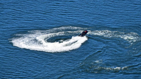 Man riding jet ski scooter over blue sea water GIF