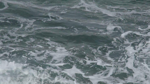 Rough sea with foamy waters of deep green color waving in dim daylight, close-up Footage
