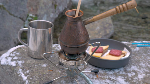 Making coffee on a portable gas burner in the mountains, on the banks of the Live Action