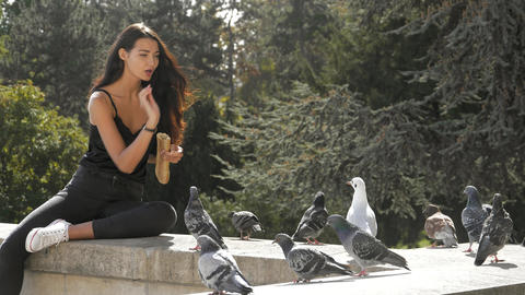Beautiful young girl feeding pigeons. Slow motion 4K footage Footage