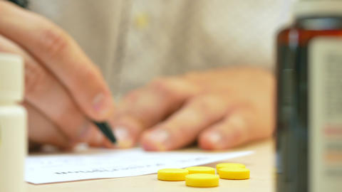 Healthcare professional doctor writing prescription for tablet pills Footage
