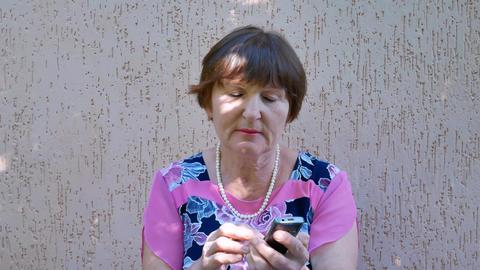Senior woman holding phone GIF