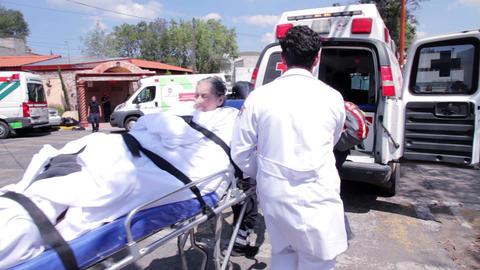Red cross paramedics carrying an elderly patient ビデオ