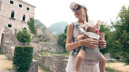 Mom and her baby travel with baby carrier backpack on summer vacation Footage