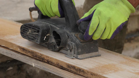 Male hands working with wooden plank electric planer Slow motion Footage