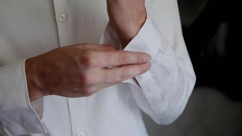Young man puts cufflinks on a white shirt GIF
