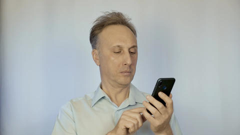 A middle aged man in a light shirt talking on the phone. It stands on a light Footage