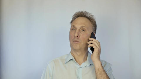 A middle aged man in a light shirt talking on the phone.... Stock Video Footage