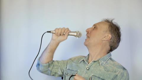 A middle aged man sings into a microphone. He has a great mood Footage