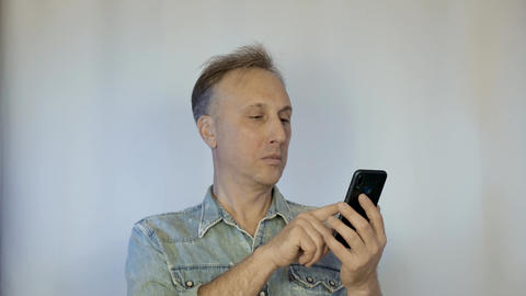 A middle aged man looks at photos on a smartphone and smiles. Nice memories GIF