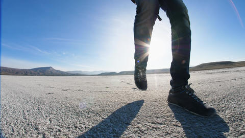 Legs walk the cover of dried up salt lake Live Action