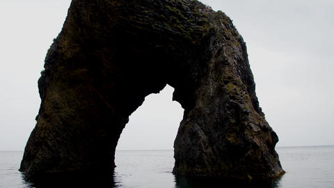 Stone grotto in the sea against a cloudy sky Footage